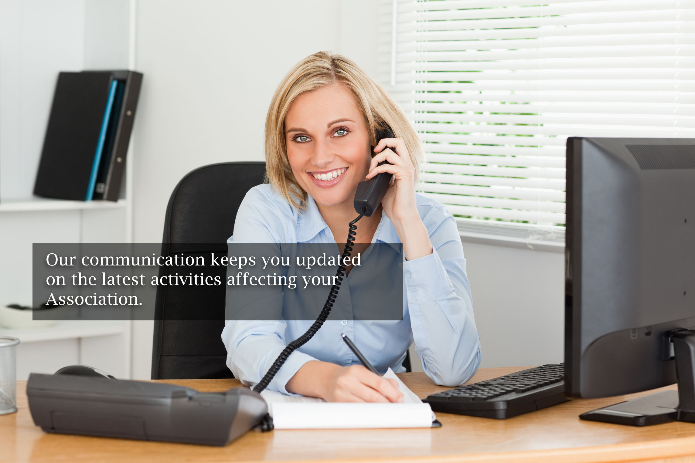 woman in association management at desk on phone
